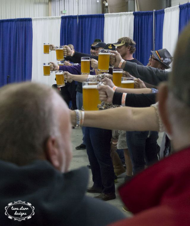 people holding beer glasses in the air in a line