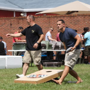 U.S. Marine Corps Capt. Christopher M. Ehlers, commanding officer, Lima Company (Lima Co.), Headquarter's and Support Battalion, School of Infantry-East throws a bean bag at the his board during a corn hole game at a cookout,  Camp Geiger, N.C., Aug. 30, 2013. Lima Co. held a cookout for students to break up the everyday grind, boost morale and emphasize safety over the Labor Day holiday. (U. S. Marine Corps photo by Staff Sgt. Christine M. Wilcox, Combat Camera, SOI-E/Released)